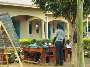 Een leraar geeft 8 kinderen buiten les in Oeganda.