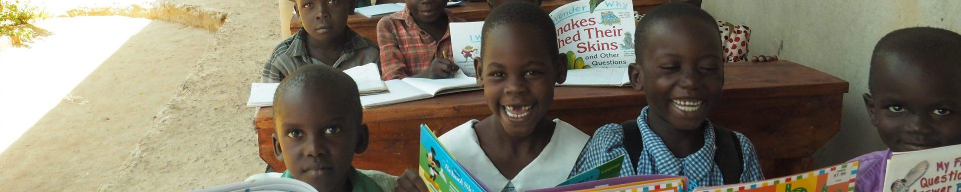 Een groep kinderen zit lachend onder een afdak tijdens schoolles.