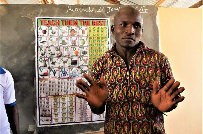 Een schoolmeester staat voor het bord in een klaslokaal in Togo.