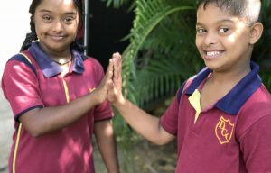 Een jongen en meisje geven elkaar een highfive in Sri Lanka.