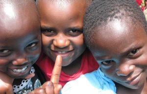 Drie schoolkinderen lachend op de foto in Rwanda.