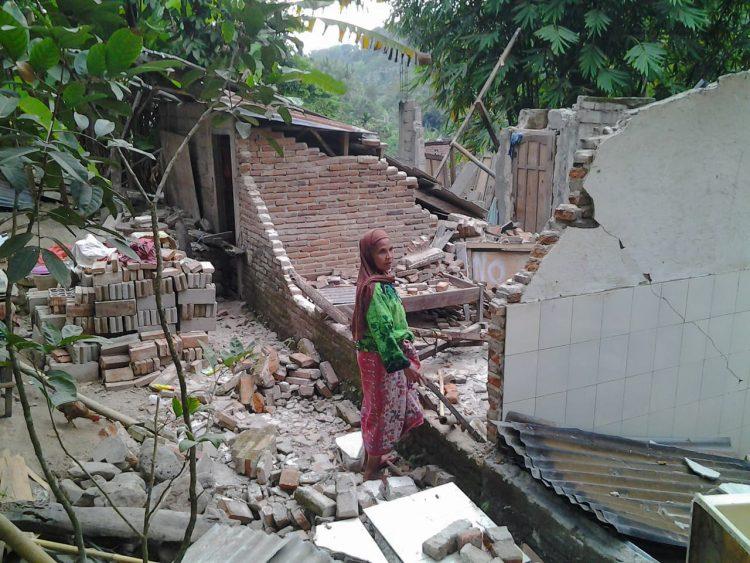 Een vrouw staat bij de resten van haar huis na een aardbeving in Lombok.