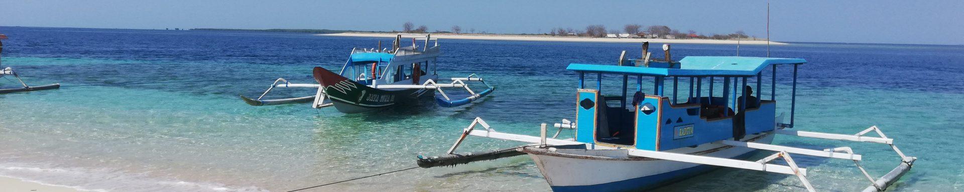 Twee boten liggen te wachten op een wit zandstrand in Lombok, Indonesië.