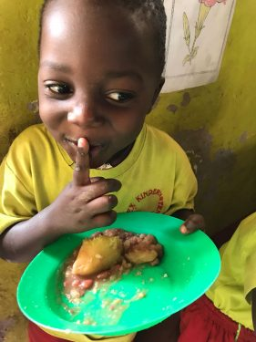 Een jongetje eet van een groen bordje op school in Oeganda.