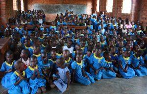 Een schoolklas met tientallen meisjes met blauwe kleren in Oeganda.
