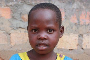 Een klein meisje in schooluniform in Oeganda.