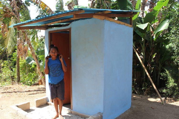 Een meisje poseert voor een nieuw gebouwde wc in Indonesië.