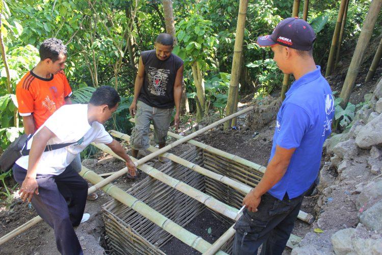 Vier mannen bouwen aan nieuwe toiletten in Indonesië.