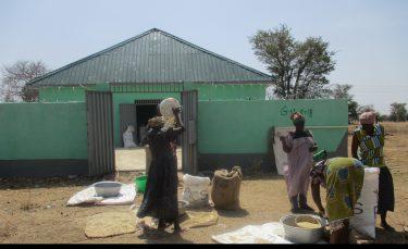 Vier vrouwen zijn aan het werk met pindas in Ghana.