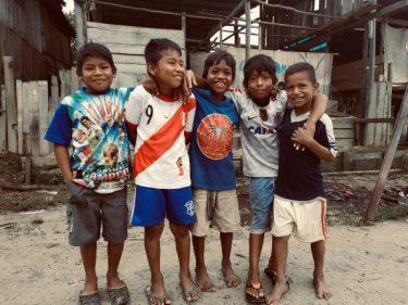Vijf jongetjes in Peru poseren lachend voor een foto.