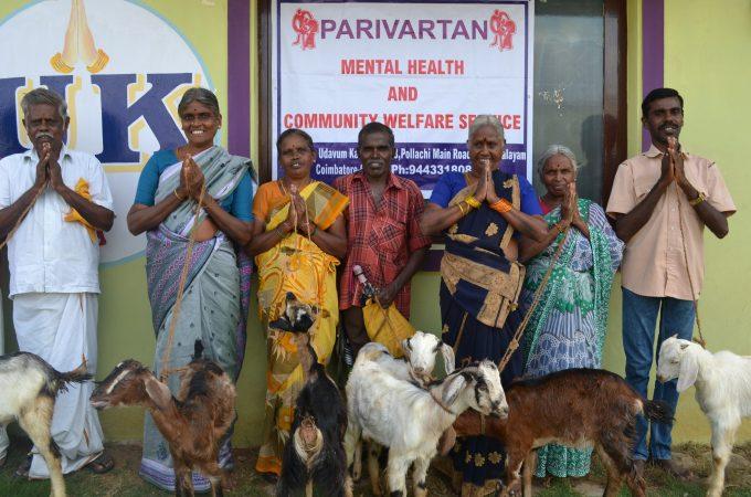 Zeven Indiaase vrouwen poseren met hun geiten in India.