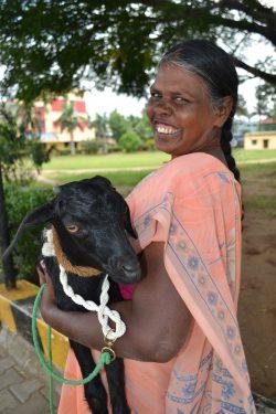 Een Indiaase vrouw met een geit in haar armen lacht in de camera.
