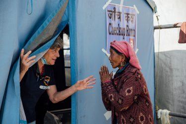 Een dokter laat een Nepalese vrouw een kliniek binnen.