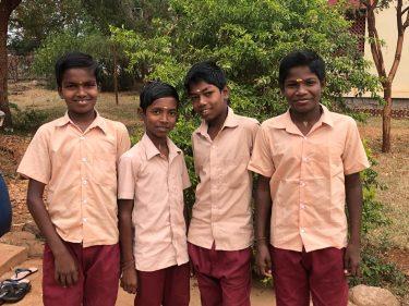 Vier jongens in schooluniform uit India poseren voor een foto.