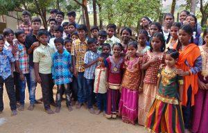 Een klas met jongens en meisjes van een school in India staat buiten.