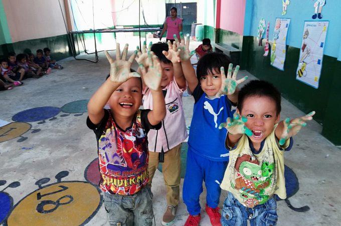 Vier kinderen met handen onder de verf steken hun vingers uit in Peru.