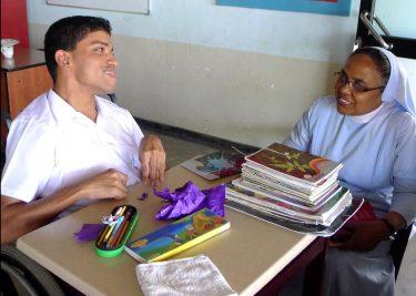 Een jongen met een beperking zit met een non op school in Nepal.