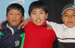 Drie jongetjes uit groep drie in een klas in Bolivia.