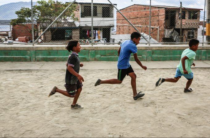 Drie straatkinderen voetballen op een pleintje in Colombia.