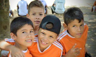 Vier straatkinderen in oranje shirts lachen naar de camera in Colombia.